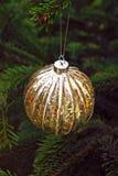 Золото и серебряный мерцающий шарик рождества на сосне стоковые изображения