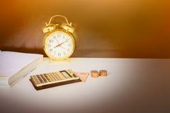 Золото калькулятора, денег и будильника старое винтажное над белой и черной предпосылкой с космосом экземпляра добавьте стиль тек Стоковое фото RF