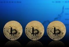 Золото монетки 3 Bitcoin на предпосылке диаграммы стоковое фото