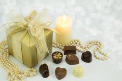 Золото присутствующее с сортированными шоколадами. Стоковое Изображение