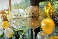 Золото торжества и белые воздушные шары с sparkles и Congratula стоковое фото