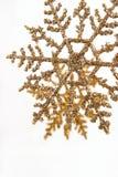 золото яркия блеска орнаментирует вертикаль снежинки Стоковое Фото