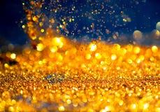 Золото яркого блеска освещает предпосылку grunge, abstrac яркого блеска defocused Стоковое Фото