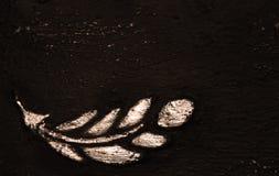 Золотые ветвь лавра, лист завода или перо на черной текстурированной предпосылке, золочении, листовом золоте стоковое изображение rf