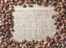 Золотые кофейные зерна расположенные как рамка на hessian с e стоковая фотография