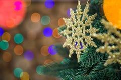 Золотые круглые снежинки вися на зеленой рождественской елке Стоковая Фотография RF
