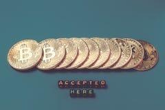 Золотые монетки при знак секретный-валюты положенный в ряд на темную предпосылку бирюзы, и ниже там принятое ` надписи стоковые фото