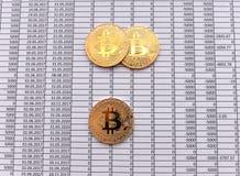 Золотые монетки Bitcoin на белой предпосылке с номерами цена bi стоковая фотография