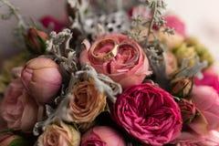 Золотые обручальные кольца лежат в бутоне розы пинка Стоковое Фото