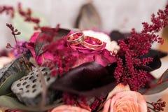Золотые обручальные кольца лежат в бутоне розы пинка Стоковые Изображения RF