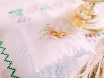 Золотые обручальные кольца лежа на белой малой подушке Стоковые Изображения RF