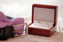 Золотые обручальные кольца на таблице перед свадебной церемонией Стоковая Фотография RF