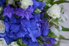 Золотые обручальные кольца с на букетом свадьбы белых и голубых цветков Стоковая Фотография