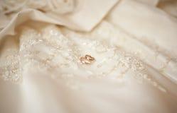 Золотые обручальные кольца smoth на silk платье свадьбы Стоковая Фотография