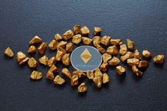 Золотые самородки и Etereum чеканят на черной конкретной предпосылке владение домашнего ключа принципиальной схемы дела золотисто Стоковые Фотографии RF