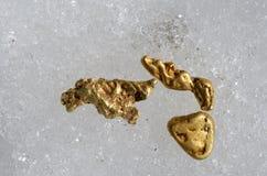 Золотые самородки на снеге принятом outdoors Стоковое Изображение