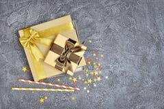Золотые сияющие классические подарочные коробки с коричневыми смычками сатинировки и бумажные соломы коктеиля с confetti в форме  стоковое фото