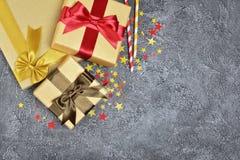 Золотые сияющие классические подарочные коробки с смычками сатинировки цвета и бумажные соломы коктеиля с confetti в форме звезд  стоковое изображение rf