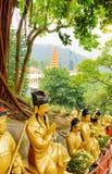 Золотые статуи Будды на предпосылке красных пагоды и landscap Стоковые Изображения RF