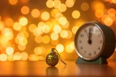 Золотые шарик и часы на предпосылке расплывчатых светов стоковая фотография rf