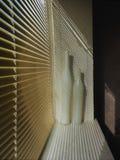 Золотые шторки металла, в белой апертуре окна там 2 вазы фарфора, от шторок вкосую тени падают, на Стоковое фото RF