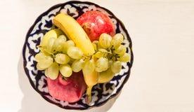 Золотые яблоко, банан, гранатовое дерево и виноградины на азиатской плите Стоковое Фото
