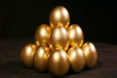 Золотые яичка на черной предпосылке стоковые изображения