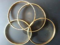 Золотые bangles золота на серой предпосылке Стоковые Изображения
