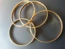 Золотые bangles золота на серой предпосылке Стоковые Фотографии RF