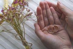 2 золотых кольца в ладонях ` s женщин Стоковое Фото