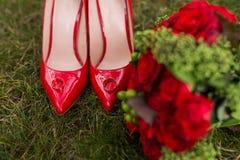 2 золотых обручального кольца лежат на ботинках красной моды женских на зеленой траве венчание Стоковое Фото