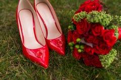 2 золотых обручального кольца лежат на ботинках красной моды женских на зеленой траве венчание Стоковое Изображение RF