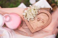 2 золотых обручального кольца на деревянной предпосылке сердца Стоковая Фотография RF