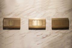 3 золотых переключателя освещения на стене, время от времени Стоковое Изображение