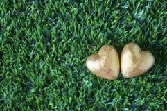 2 золотых сердца на предпосылке зеленого стекла Влюбленность ценный c Стоковые Фото