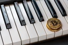 2 золотых bitcoins на клавиатурах рояля стоковые изображения rf