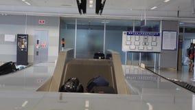 Зона заявки багажа в аэропорте Чемоданы на конвейерной ленте видеоматериал