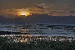 Зона китайского рыбацкого поселка intertidal в заходе солнца стоковое изображение rf