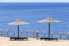 2 зонтика пляжа с деревянными loungers солнца рядом с Красным Морем Стоковое Изображение RF