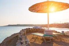 Зонтики и пустые deckchairs на пляже во время захода солнца Стоковое Фото