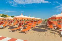 Зонтики и салоны фаэтона на пляже Римини в Италии стоковая фотография