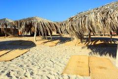 Зонтики и циновки на пляже Стоковое Фото