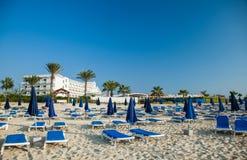 Зонтики и deckchairs навеса на красивом пляже Стоковое Фото