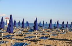Зонтики и deckchairs на пляже на заходе солнца на seashore Стоковые Фото