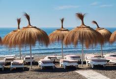 Зонтики и deckchairs на пляже для туристов Стоковая Фотография