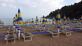 Зонтики и loungers солнца на пляже Стоковые Изображения