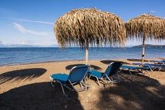 Зонтики и sunbeds соломы на песчаном пляже, Корфу, Греции Стоковое Изображение