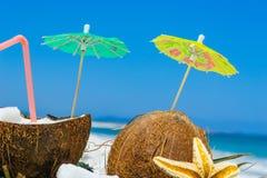 Зонтики коктеиля в половинах кокосов Стоковая Фотография