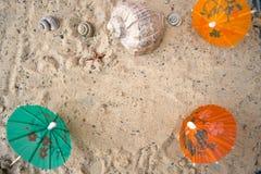 Зонтики коктеиля на песке солнечного пляжа Стоковое Фото