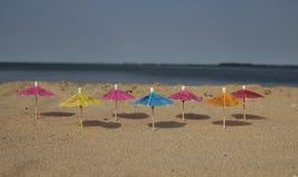 Зонтики красят на песке на пляже Стоковые Изображения RF